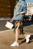一双裙子、牛仔布夹克和白色运动鞋的时髦的女孩在hu 免版税库存图片