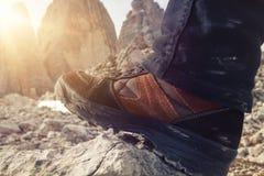 一双远足的鞋子的特写镜头,太阳通过山发光 库存图片