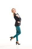 一双黑夹克、紫色裤子和鞋子的美丽的白肤金发的女孩有脚跟的 免版税库存图片