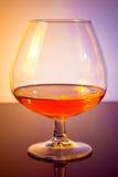 一口威士忌酒在典雅的典型的科涅克白兰地玻璃的白兰地酒在色的轻的迪斯科背景 免版税库存图片