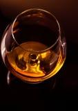 一口威士忌酒看法上面在典雅的典型的科涅克白兰地玻璃的白兰地酒在与金黄反射的黑暗的背景 库存照片