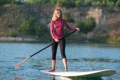 一口站立paddleboarding明轮轮叶的妇女 免版税库存图片