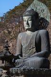 一古老金属雕刻坐的和平菩萨在树山前面和绘与绿色在大历史 免版税库存照片
