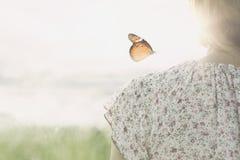 一只五颜六色的蝴蝶在女孩的肩膀精美地倾斜 免版税库存照片
