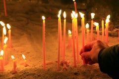 一只人的手在健康投入一个蜡烛在教会 库存照片