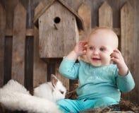 一只可爱的女婴和小的白色兔子的画象 免版税库存图片