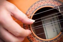一只吉他弹奏者手的特写镜头有吉他的 免版税库存图片