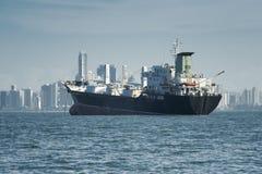 一只大货船的看法停住和城市地平线在背景 免版税库存照片