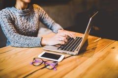 一只女孩` s手的特写镜头在灰色毛线衣用途膝上型计算机技术在咖啡馆的一张木桌上 在手机和gl附近 免版税库存图片