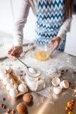 一只女孩` s手的特写镜头有匙子的在厨房里采取鸡蛋的糖 免版税库存照片