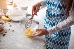 一只女孩` s手的特写镜头有笤帚的搅动鸡蛋 免版税库存图片