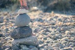 一只女性手投入一块小石头在石头顶部金字塔  库存照片