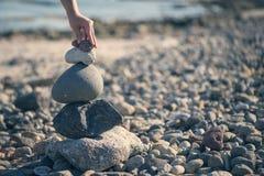 一只女性手投入一块小石头在石头顶部金字塔  图库摄影