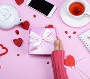 一只女性手拿着有一把弓的一个桃红色箱子在桌 免版税图库摄影