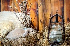 一只小兔子在篮子坐乱丢与干草 在兔子附近有一盏老灯和在它后是分支  免版税库存图片
