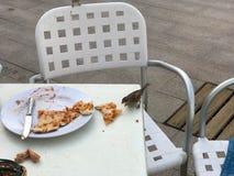 一只小鸟,麻雀吃从一张白色桌的一个可口薄饼在街道上的一个室外咖啡馆 免版税图库摄影