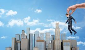 一只巨型手拿着在一个大商业区的一个小商人有许多摩天大楼的 库存照片