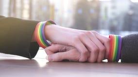 一只手为其他到达与在街道的背景的LGBT镯子,在桌上 股票视频