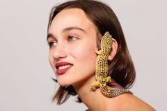 一只手扶的鬣鳞蜥壁虎爬行在一个女孩的面孔y 在一个灰色背景 里面 免版税库存照片