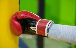 一只手的片段在拳击红色手套的击中一个黄色梨, a 免版税库存照片