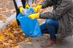 一只手的特写镜头在手套的去除在垃圾袋的塑料瓶 免版税库存图片