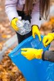 一只手的特写镜头在手套的去除在垃圾袋的塑料瓶 库存图片