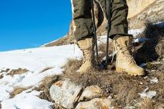 一只旅游` s脚的特写镜头在迁徙的起动的用北欧人走的站立的棍子在山的一块岩石石头 免版税库存图片