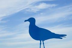 一只海鸥的蓝色铁剪影与天空的在背景中 免版税库存图片