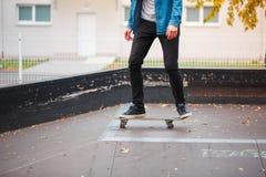 一只溜冰板者` s脚的特写镜头在秋天冰鞋公园 库存图片