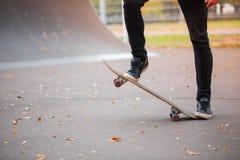一只溜冰板者` s脚的特写镜头在秋天冰鞋公园 库存照片