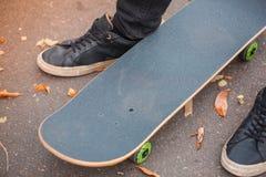 一只溜冰板者` s脚的特写镜头在黑运动鞋的 库存图片