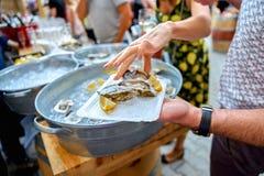 一只牡蛎的特写镜头用一个柠檬,象快餐 妇女是pickin 免版税库存照片