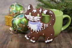 以一只猫的形式圣诞节曲奇饼与绿色杯子 免版税库存图片