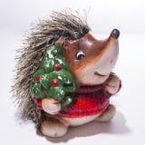 一只猬的小雕象在圣诞节红色毛线衣的有Christma的 免版税库存图片