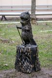 一只猬的滑稽的装饰雕象在滑雪的在一个树桩在公园 免版税图库摄影