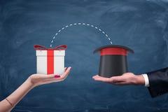 一只男性商人` s手拿着巫术师帽子的和拿着有连接的小点的一只女性手一个礼物盒之间 库存图片