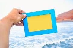 一只男性手拿着与空的空间海景的一个蓝色照片框架在背景 汽车城市概念都伯林映射小的旅行 库存照片