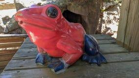一只红色和蓝色青蛙的雕象 免版税库存图片