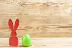 一只红色复活节兔子和一个绿色复活节彩蛋 库存照片