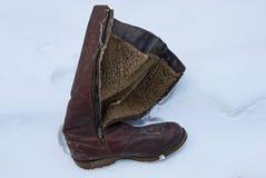一只老和肮脏的棕色皮靴在白雪随风飘飞的雪站立  免版税库存照片