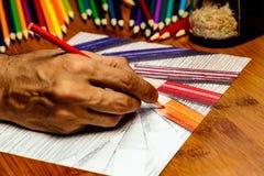 一只艺术家手在使用画色的铅笔的工作上色了pe 免版税库存图片