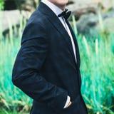 一只蓝色衣服、白色衬衣和领带蝴蝶的特写镜头新郎握在口袋的手在绿色灌木的背景 免版税图库摄影
