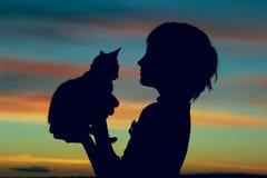 一只逗人喜爱的小女孩和小猫的播种的射击在日落 免版税库存照片