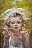 一只金黄笼子的美丽的白肤金发的女孩 免版税库存照片