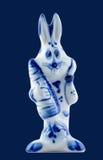 一只陶瓷兔子用一棵红萝卜在bluу隔绝的手上 库存图片