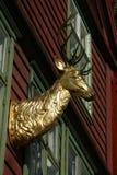 一只雄鹿的头在金子的作为墙壁装饰 图库摄影