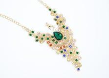 以一只鸟的形式珍贵的项链与美丽的绿色和五颜六色的石头时尚样式的概念 免版税库存图片