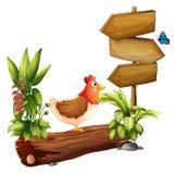 一只鸡和一只蝴蝶在木箭头附近 免版税库存图片