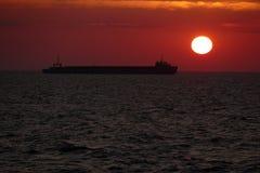 一只货船的剪影在日落的 免版税库存图片