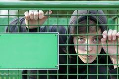 一只绿色笼子的十几岁的男孩 免版税库存图片